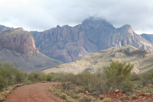 A dirt road on the bottom left that leads to Baboquivari Peak, top right, which is shrouded by a cloud.